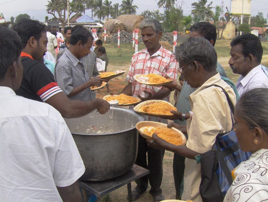 men gather around a hot meal at embrace a village